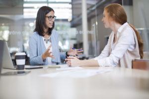 Jobbveileder og jobbsøker sitter ved et arbeidsbord.