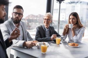 Fire kollegaer sitter rundt et bord og prater.