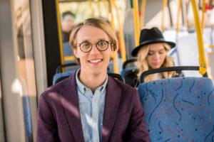 Ung mann med briller smiler til kameraet på bussen.