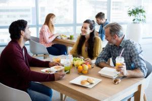 To menn og en kvinne sitter rundt et bord med mat og drikke.