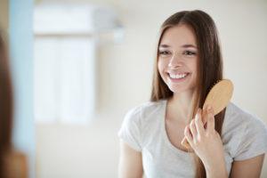 Ung kvinne børster håret med en hårbørste.