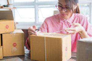 Ung kvinne jobber med å pakke kartonger med varer.