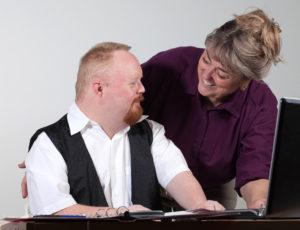 Mann og kvinne jobber sammen ved en PC.