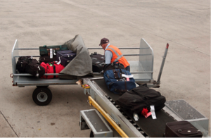 Mann jobber med å flytte kofferter ute på flyplassen