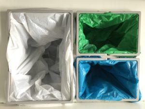 Nærbilde av tre beholdere for kildesortering, med forskjellige fargede poser til ulikt avfall.